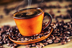 Schale schwarzer Kaffee und verschüttete Kaffeebohnen Süßes Hörnchen und ein Tasse Kaffee im Hintergrund Stockbilder