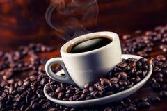 Schale schwarzer Kaffee und verschüttete Kaffeebohnen Stockbild