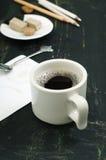 Schale schwarzer Tee, Bonbons und Bleistifte auf einem dunklen Hintergrund Stockbild