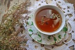 Schale schwarzer Tee mit Thymian u. Häkelarbeit Doily auf einem Retro- Hintergrund Lizenzfreie Stockfotos