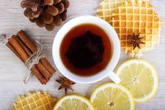 Schale schwarzer Tee mit Weihnachtsdekor, Zitrone, pinecone, Waffeln, badian und Zimt Stockbilder