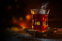 Schale türkischer Tee auf Untertasse auf rustikalem Holz mit Schnee vor einer Dunkelheit verwischte Hintergrund mit roten und gol Lizenzfreie Stockfotografie