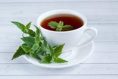 Schale tadelloser Tee und ein Bündel der Minze auf dem Tisch Stockfotografie