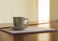Schale und ein Stapel Papiere auf seinem Schreibtisch Lizenzfreie Stockbilder