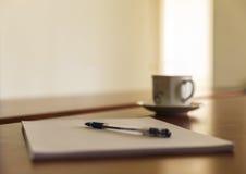 Schale und ein Stapel Papiere auf seinem Schreibtisch Stockfoto