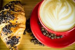 Schale und Hörnchen Coffe mit Bohnen auf Platte Stockbilder