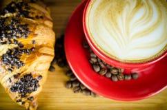 Schale und Hörnchen Coffe mit Bohnen auf Platte Lizenzfreies Stockbild