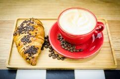 Schale und Hörnchen Coffe mit Bohnen auf Platte Stockbild
