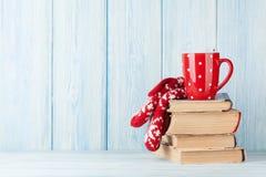 Schale und Handschuhe der heißen Schokolade über Büchern stockfotos