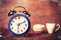 Schale und kleiner Kuchen mit Uhr Stockbilder