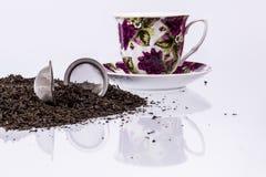 Schale und schwarzer Tee auf weißem Hintergrund. Lizenzfreie Stockfotografie