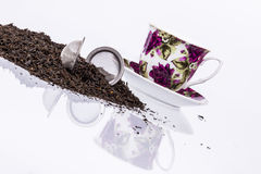 Schale und schwarzer Tee auf weißem Hintergrund. Stockbild
