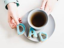 Schale wohlriechender Tee und Kekse in Form von Buchstaben D A D Lizenzfreies Stockfoto