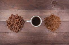 Schale zwischen Handvoll Bohnen und Instantkaffee Stockbild