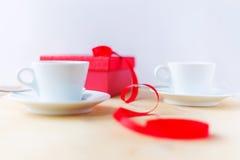 Schalen mit Kaffee, Geschenkbox, verziert durch Band auf Holztisch Lizenzfreies Stockfoto