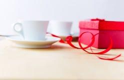 Schalen mit Kaffee, Geschenkbox, verziert durch Band auf Holztisch Stockfotografie