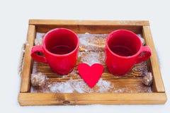 Schalen mit Tee im Schnee, Valentinsgruß ` s Tag Stockbild