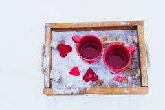Schalen mit Tee im Schnee, Valentinsgruß ` s Tag Lizenzfreie Stockfotos