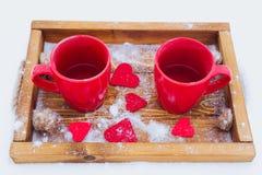 Schalen mit Tee im Schnee, Valentinsgruß ` s Tag Lizenzfreie Stockbilder