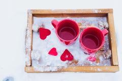 Schalen mit Tee im Schnee, Valentinsgruß ` s Tag Lizenzfreie Stockfotografie