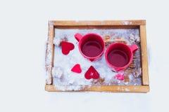 Schalen mit Tee im Schnee, Valentinsgruß ` s Tag Stockfotografie