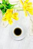 Schalen schwarzer Kaffee über weißem Holztisch mit gelben Tulpen Lizenzfreies Stockfoto
