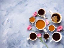 Schalen und Becher Kaffee und Blumen Stockfotografie