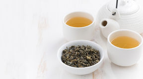 Schalen und Teekanne mit grünem Tee auf einem weißen hölzernen Hintergrund Lizenzfreie Stockfotos