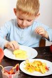 Schalenapfel des kleinen Jungen, der zu Hause kocht Lizenzfreie Stockfotos