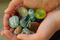 Schalenförmige Hände mit kleinen Steinen Stockfotografie