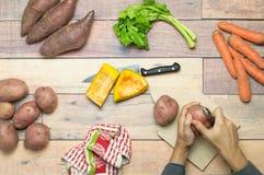 Schalenkartoffeln zusammen mit Süßkartoffeln, Karotten, Kürbis und Sellerie auf Holztisch für das Kochen Lizenzfreie Stockbilder
