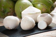 Schalenkokosnuß auf Matte mit grünem Kokosnusshintergrund Stockfotos