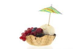 SchalenVanilleeis mit Frucht und Sonnenschirm Lizenzfreies Stockfoto
