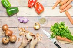 Schalenzwiebeln zusammen mit Pfeffern, Karotten, Knoblauch und Petersilie auf dem Tisch Stockbilder
