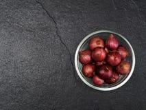 Schalottenlök i en glass bunke med mörk bakgrund Fotografering för Bildbyråer