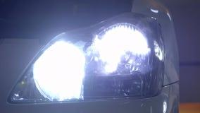 Schalten Sie die Scheinwerfer des Autos in einer dunklen Steingarage ein stock video