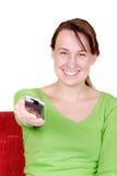 Schalter der jungen Frau mit Fernbedienung Lizenzfreies Stockfoto
