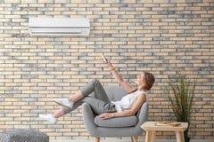 Schaltung der jungen Frau auf Klimaanlage lizenzfreies stockbild