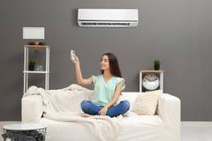 Schaltung der jungen Frau auf Klimaanlage stockbild