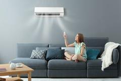 Schaltung der jungen Frau auf Klimaanlage lizenzfreie stockfotografie