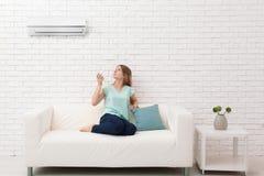 Schaltung der jungen Frau auf Klimaanlage lizenzfreies stockfoto
