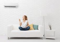 Schaltung der jungen Frau auf Klimaanlage lizenzfreie stockfotos
