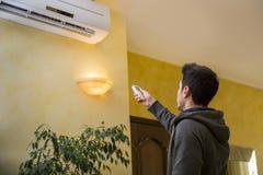 Schaltung des jungen Mannes auf der Klimaanlage lizenzfreies stockfoto