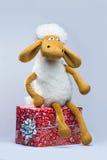 Schapen met een Kerstmisgift op witte achtergrond wordt geïsoleerd die Stock Fotografie