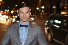 Scharf gekleideter kaukasischer Mann in Gray Suit At Night in der Stadt Lizenzfreie Stockfotos