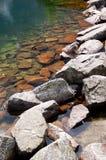 Scharfe Felsen auf dem Ufer von einem Gebirgssee Stockbild