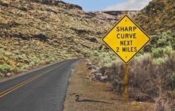 Scharfe Kurve als Nächstes 2 Miles Sign Lizenzfreies Stockfoto