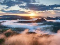 Scharfe Spitzen erhöhten sich vom rosa Nebel im langen Tal Lizenzfreies Stockbild