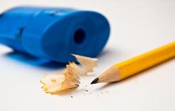 Scharfer gelber Bleistift mit blauem Bleistiftspitzer Stockbilder