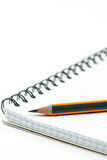 Scharfer hölzerner Bleistift auf dem Schulnotizbuch über weißem backgroun Stockfotografie